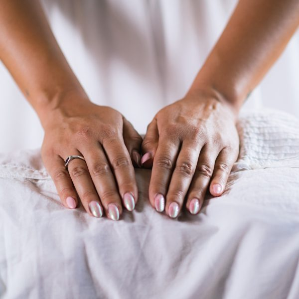 Female Therapist Performing Reiki Therapy Treatment. Hands Over Woman's Stomach. Alternative Therapy Concept, Stress Reduction and Relaxation.